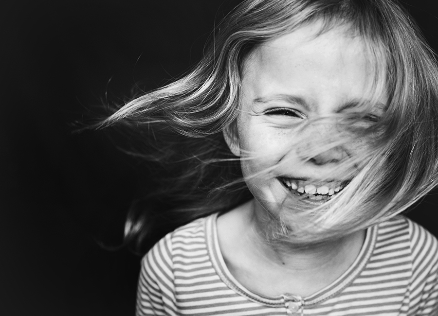 Motion-Blur-in-Black-and-White-Portrait-of-Child-Laughing-and-Hair-Blowing-by-Anne-Dale