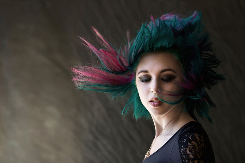 portrait of woman with movement in her hair and downward visual flow by Jamie Bates