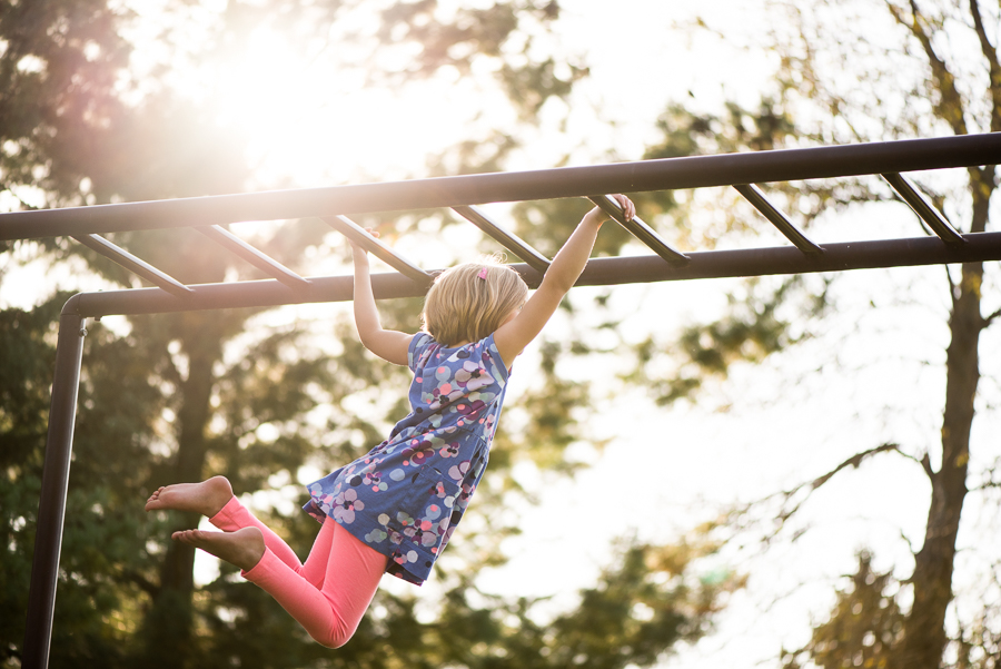 Suspended-Movement-of-Child-Swinging-on-Monkey-Bars-in-Beautiful-Light-by-Photographer-Hannah-Fenstermacher