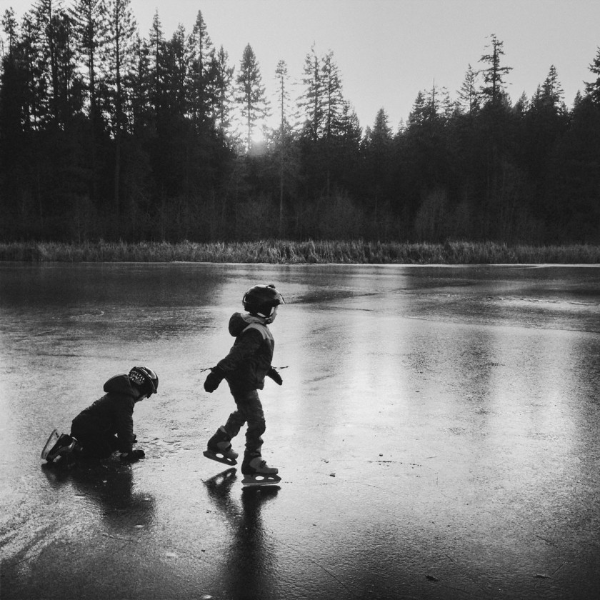 black and white photo of kids ice skating by Kim Hildebrand