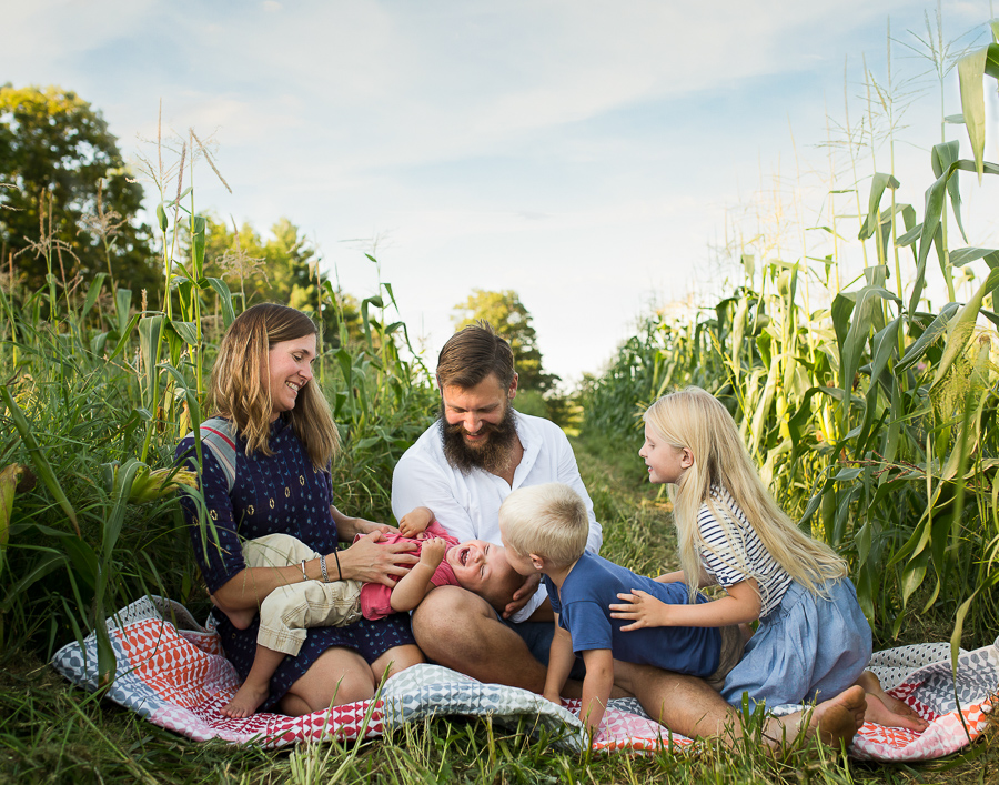 family laughing together in a cornfield by Kristy Dooley