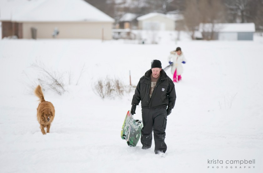 family snow sledding with dog by Krista Campbell