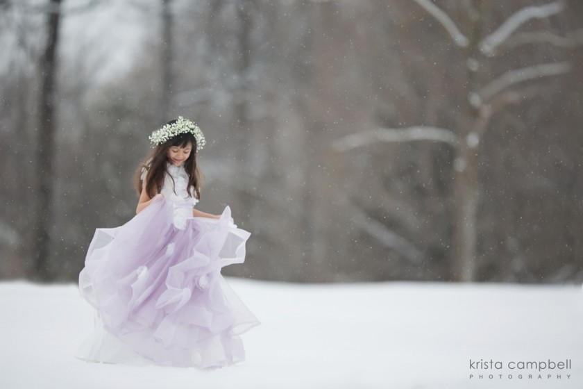 girl in purple dress playing in the snow by Krista Campbell