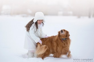 girl playing in the snow with her daughter by Krista Campbell