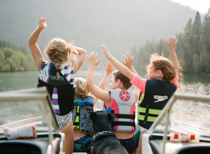 kids on a boat with their arms up by Kim Hildebrand
