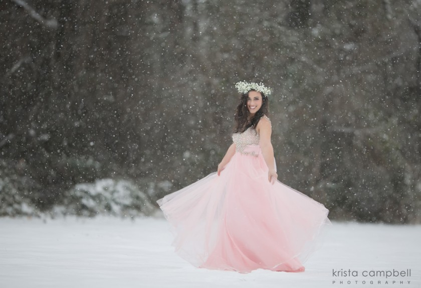 teen twirling her dress int he snow wearing a flower crown by Krista Campbell