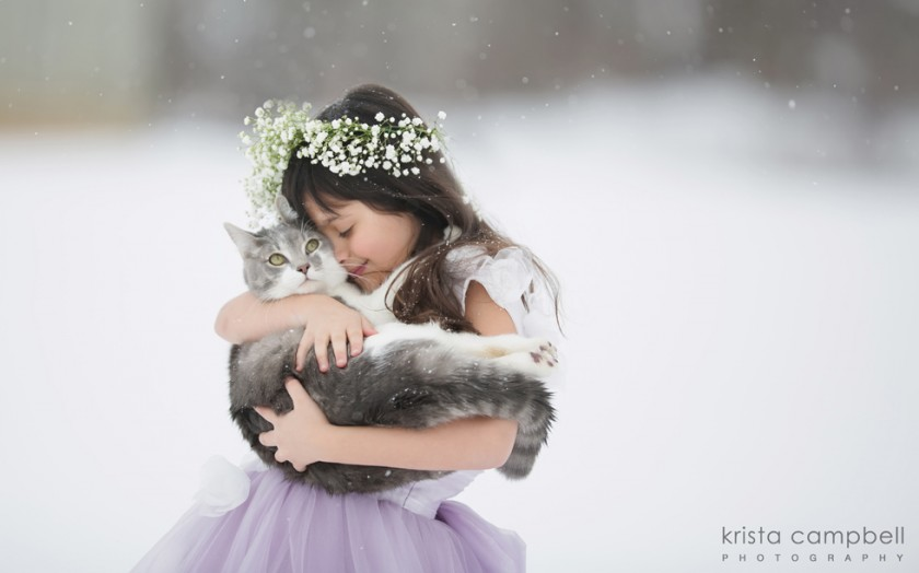 young girl in purple dress and flower crown holding a cat in the snow by Krista Campbell