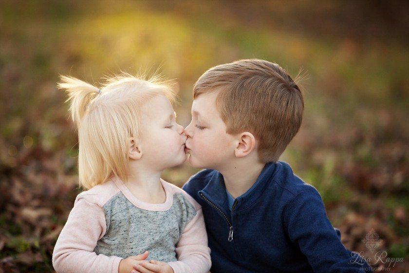 brother and sister giving each other a kiss by Lisa Rappa
