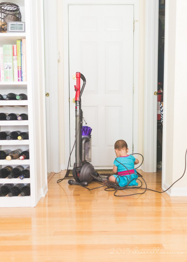 child playing with vacuum cords by Elise Cellucci