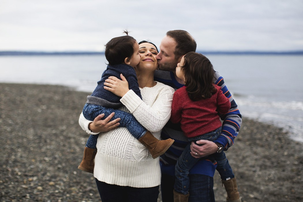 family hugging and kissing portrait by Elena Blair