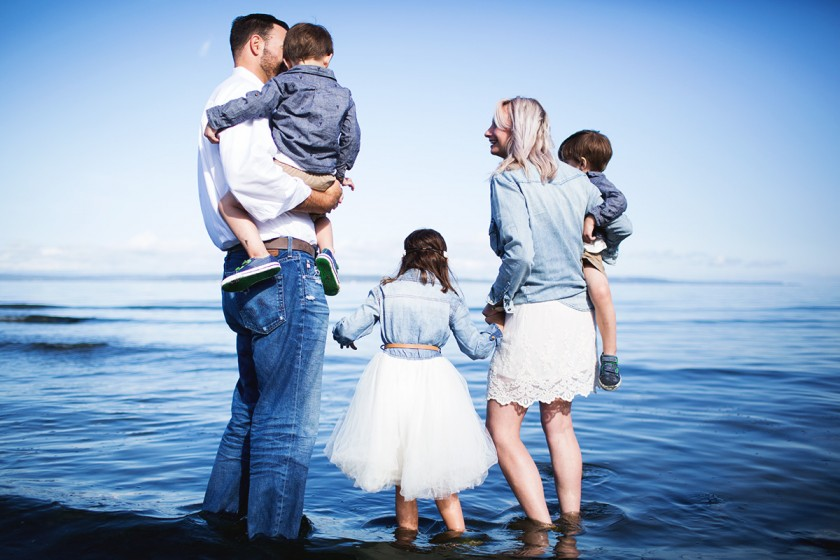 family of 5 portrait in the water by Elena Blair