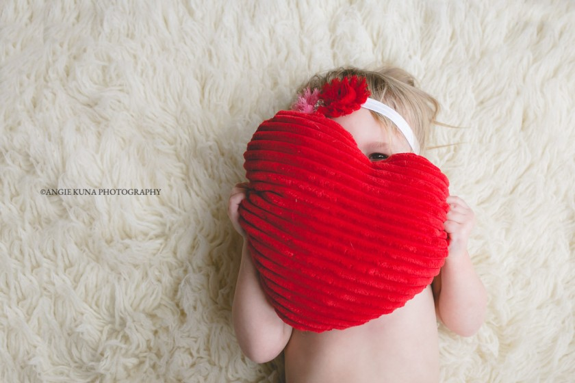 girl holding a red heart pillow by Angie Kuna