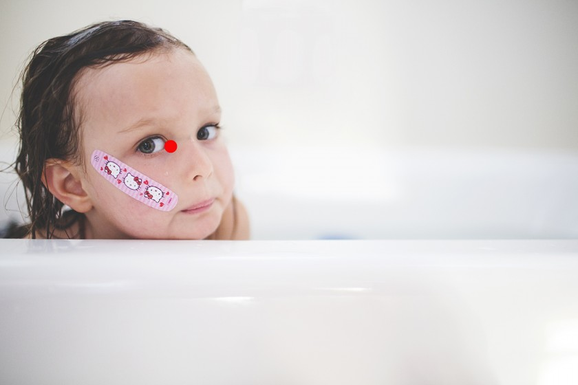 photo of girl wearing a bandaid on her face by Elena Blair