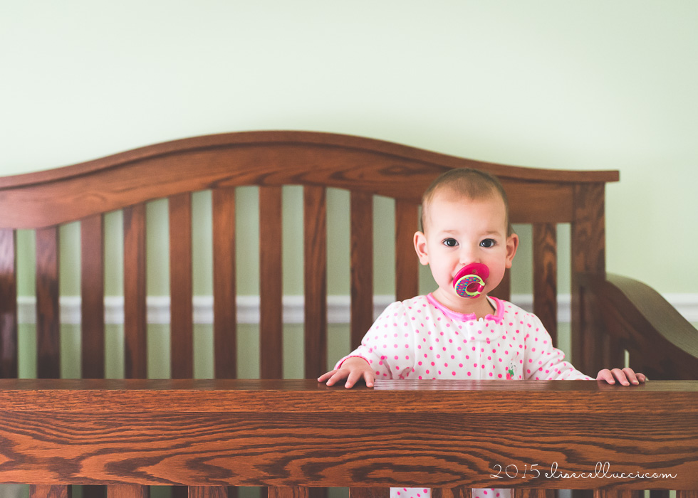 toddler standing in her crib with a pacifier pink ballerina outfit on a hanger by Elise Cellucci