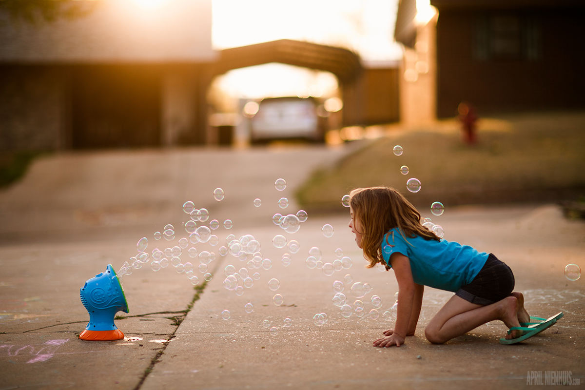 backlit photo of girl looking into bubble machine by April Nienhuis