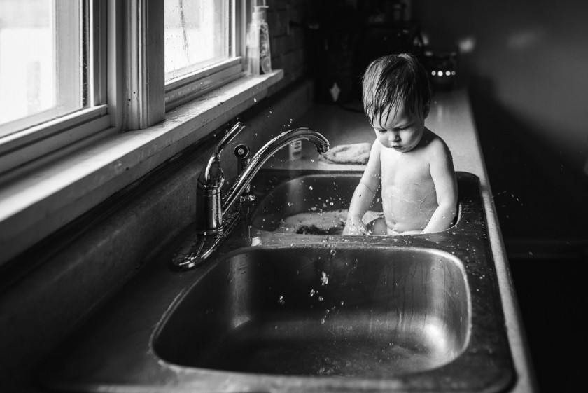 black and white photo of kid getting a sink bath by Heather Mohr