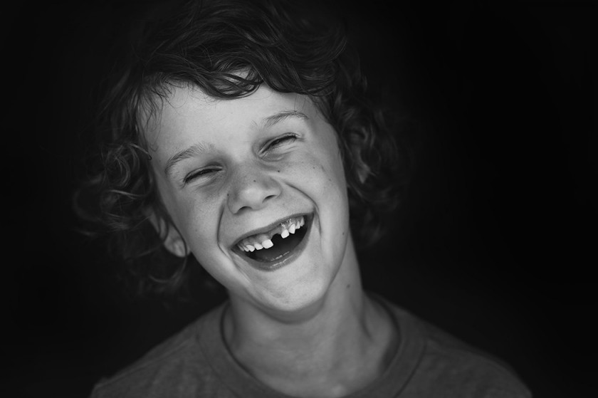black and white portrait of boy laughing by Kellie Bieser
