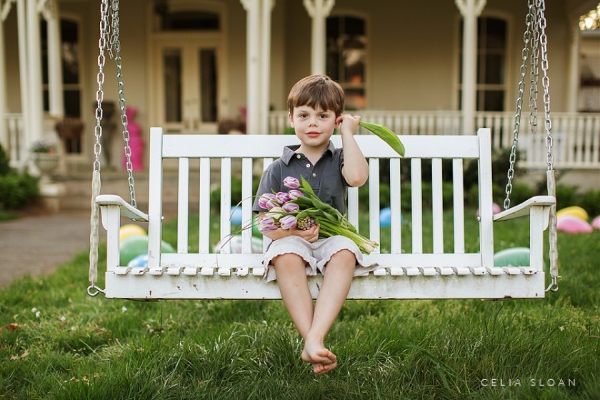 boy sitting on porch swing with tulips by Celia Sloan
