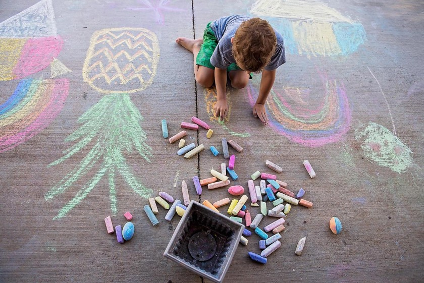 child drawing with sidewalk chalk by Allison Gipson