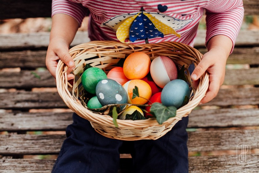 child holding a basket of Easter eggs by Juliette Fradin