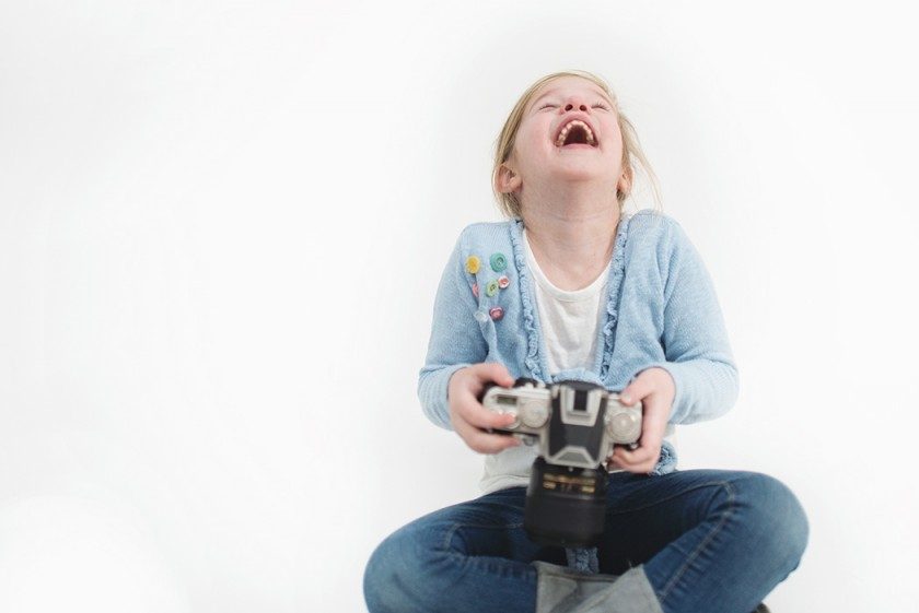 girl laughing at photos by Kellie Bieser