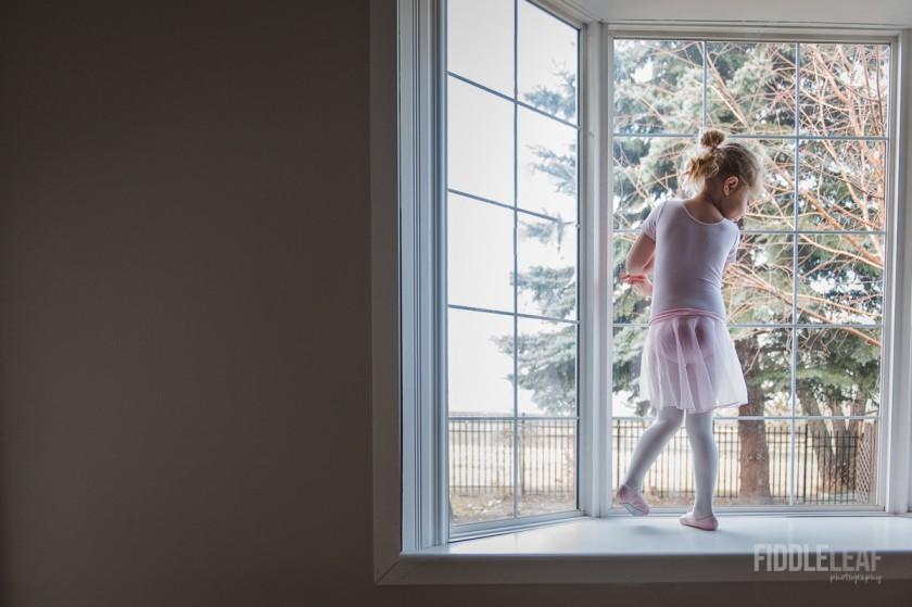 girl standing in a bay window wearing a ballerina costume by Kelly Marleau