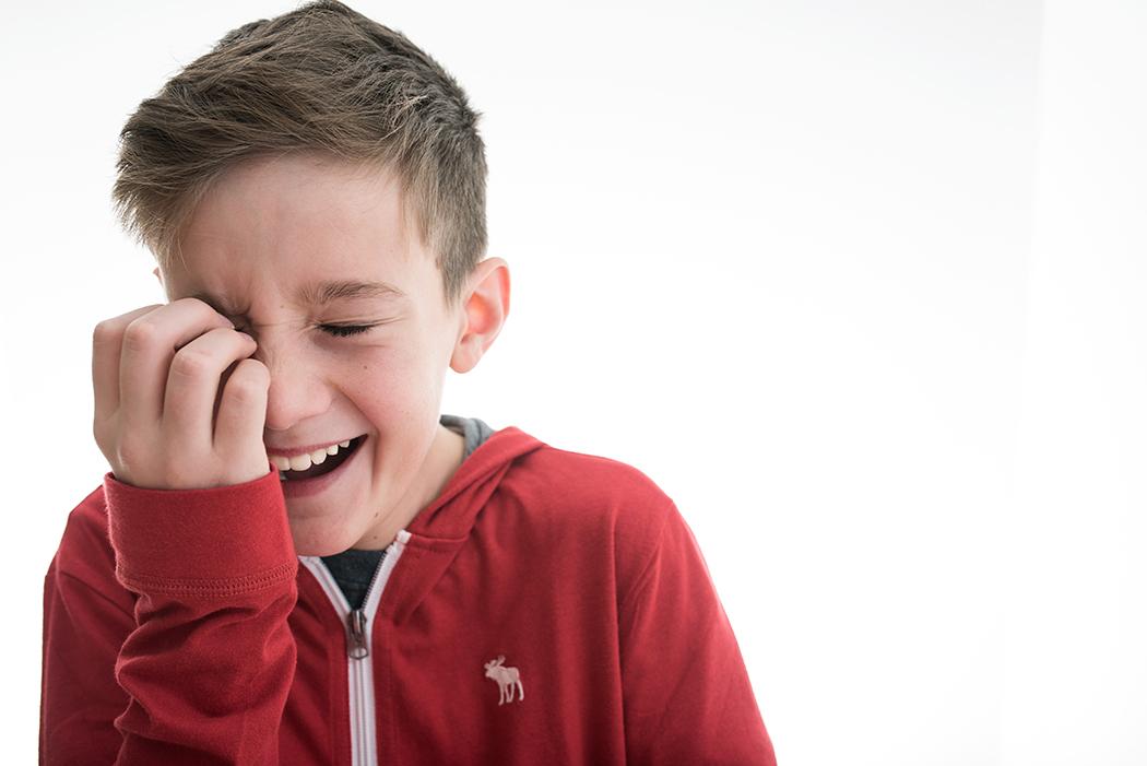 high key photo of boy in a red sweatshirt laughing by Kellie Bieser