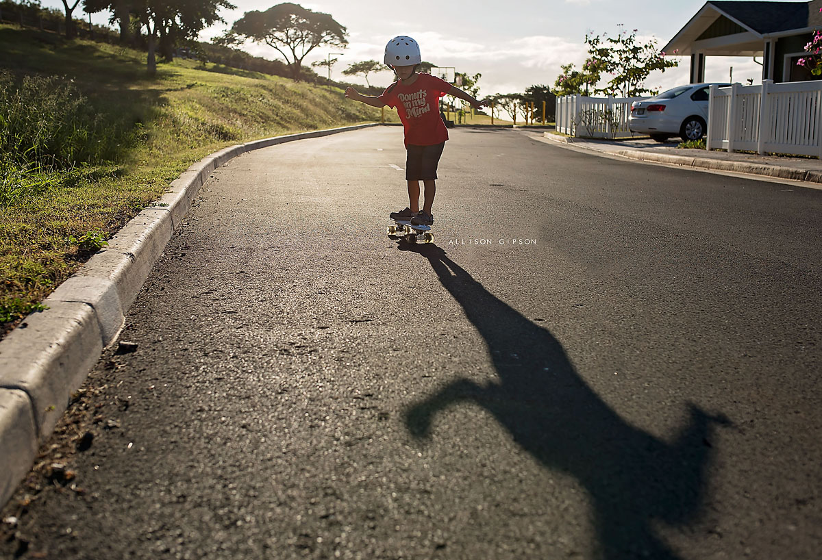 kid skateboarding down the street by Allison Gipson