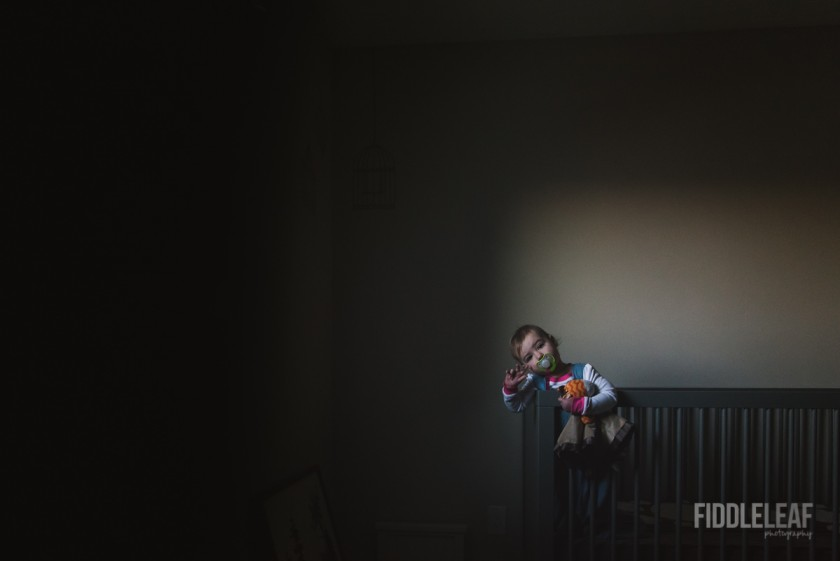 low light photo of toddler standing in crib by Kelly Marleau