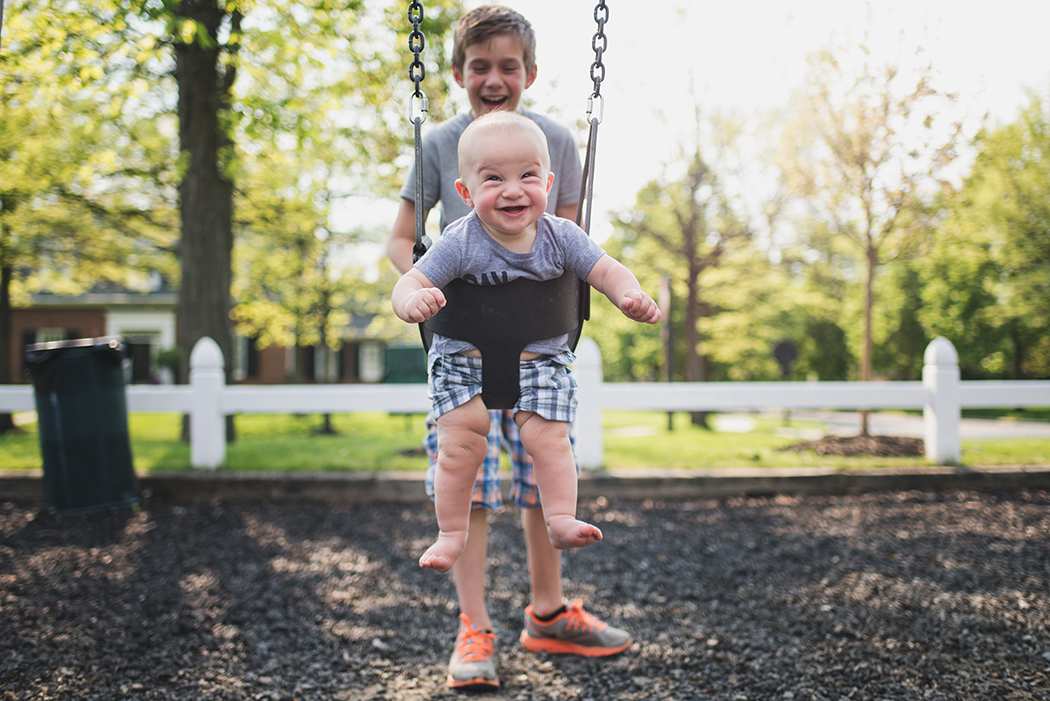 toddler boy swinging and smiling by Kellie Bieser