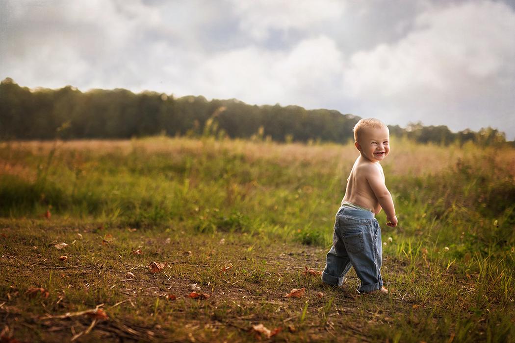 toddler boy walking in a field by Kellie Bieser