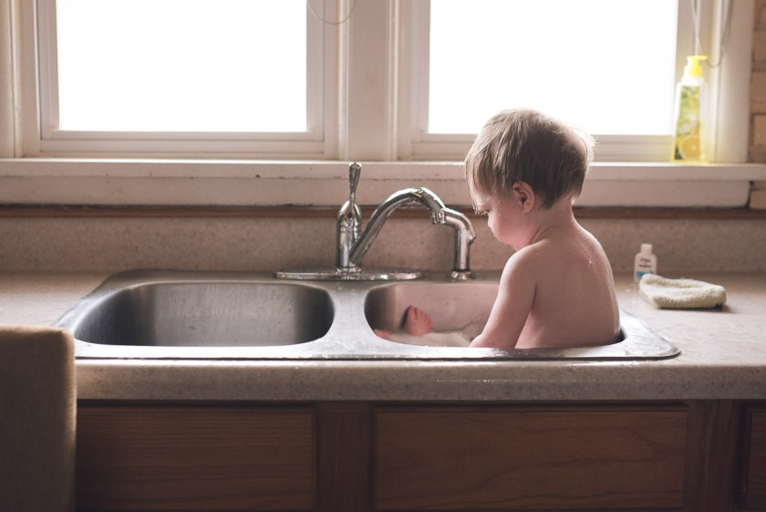 toddler getting a sink bath by Heather Mohr