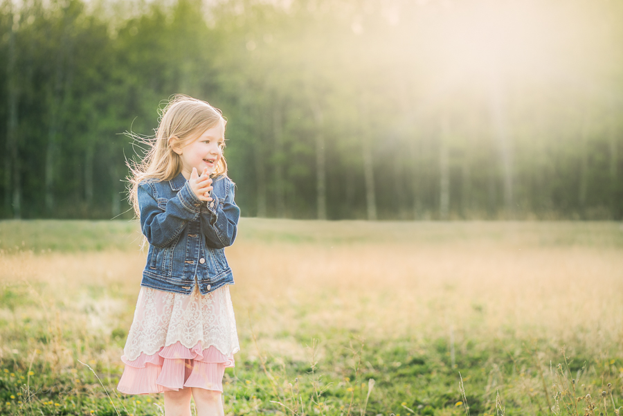 backlit photo of young girl wearing a jean jacket in a field by Gina Yeo