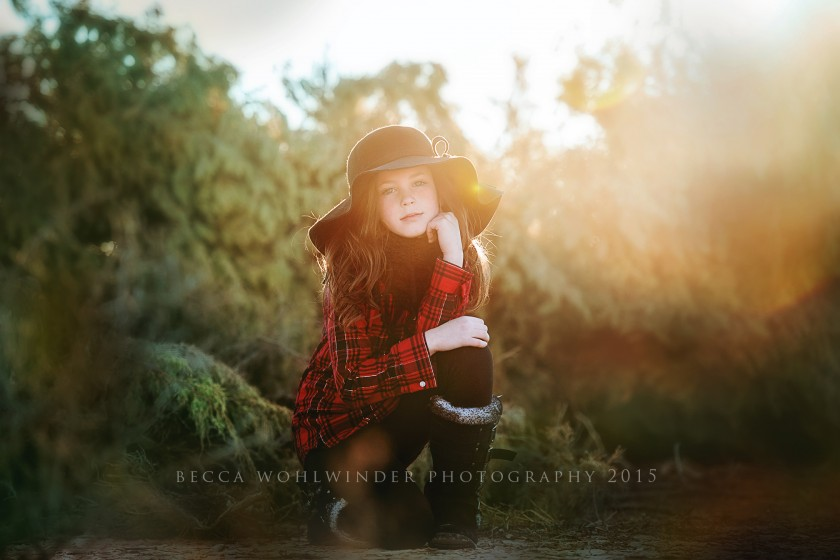 backlit picture of girl in a plaid shirt by Becca Wohlwinder