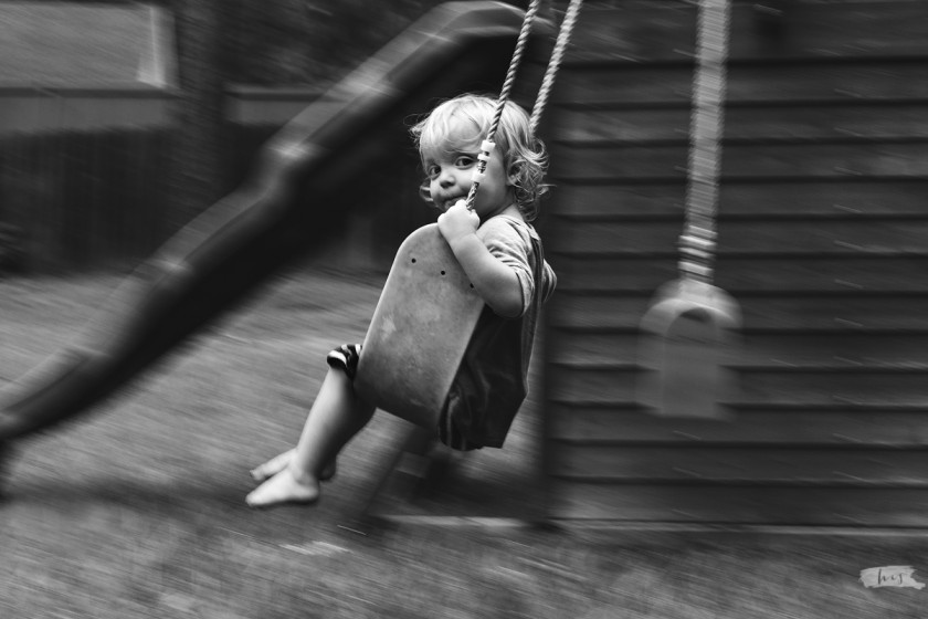 Black and white panning photo of boy swinging by heather stockett