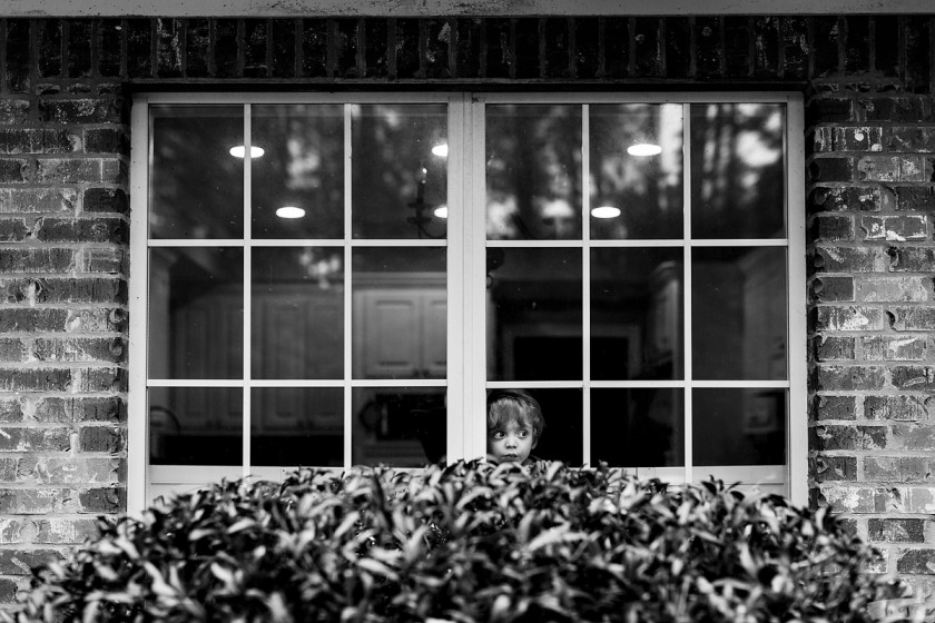 black and white photo of boy looking out a window by Heather Stockett