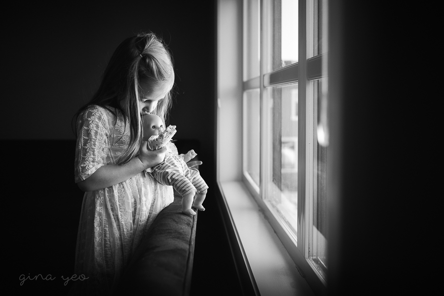 black and white photo of girl holding baby doll by window by Gina Yeo