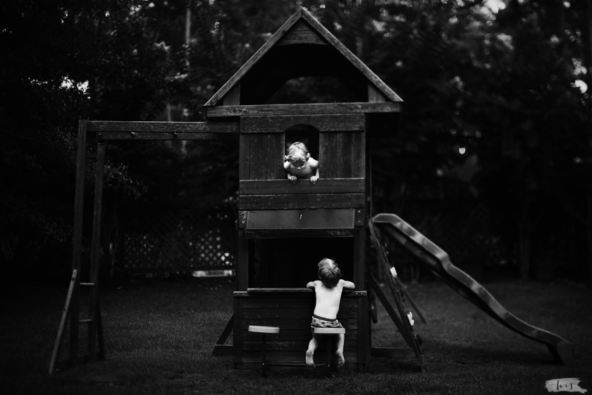 black and white picture of twins playing on a swing set by Heather Stockett