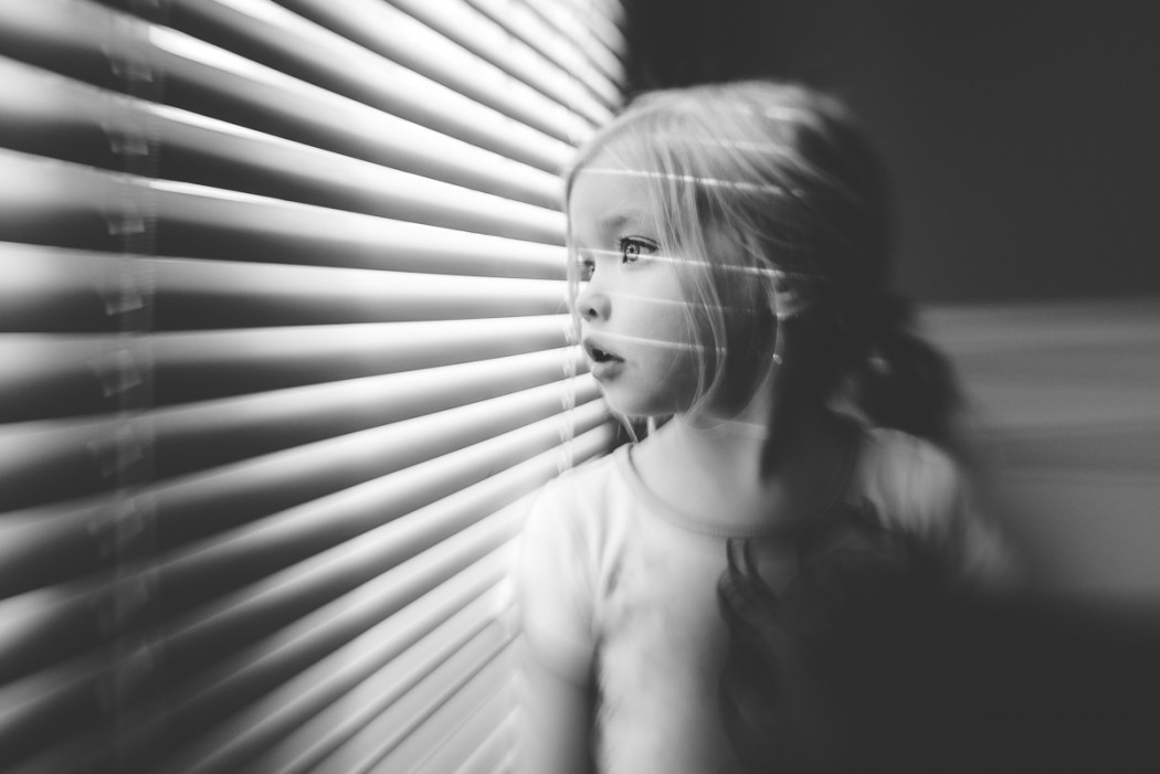 black and white picture of young girl looking out the blinds by Tiffany Kelly