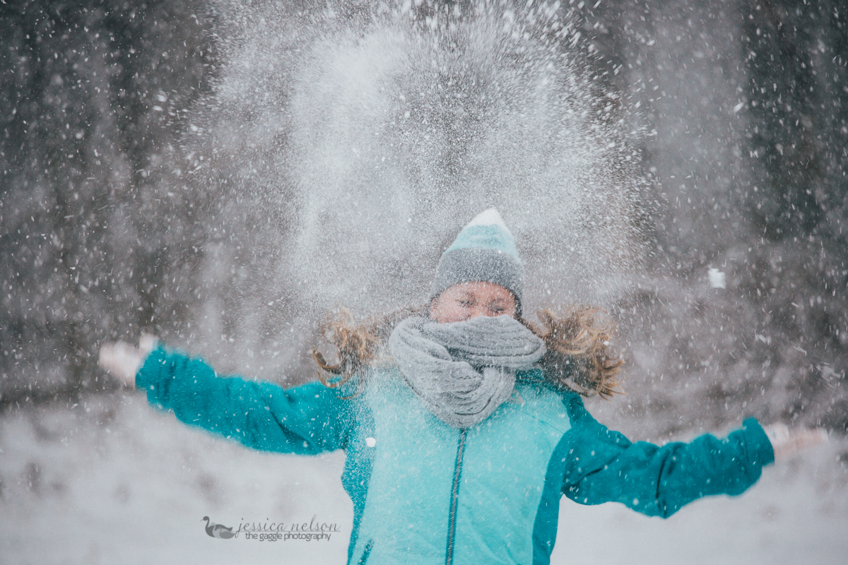 girl in blue coat throwin snow by Jessica Nelson