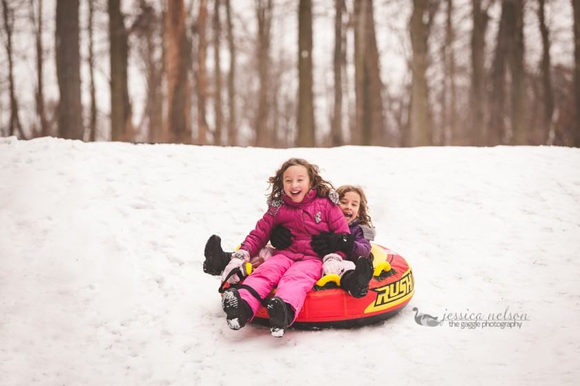 girls riding down a tube on the snow by Jessica Nelson