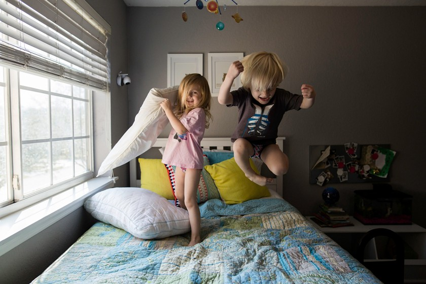 happy picture of twins jumping on the bed by Jennifer Kielich