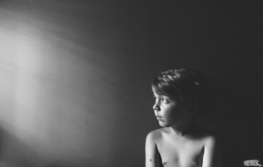 natural light picture of boy looking out a window by Heather Stockett
