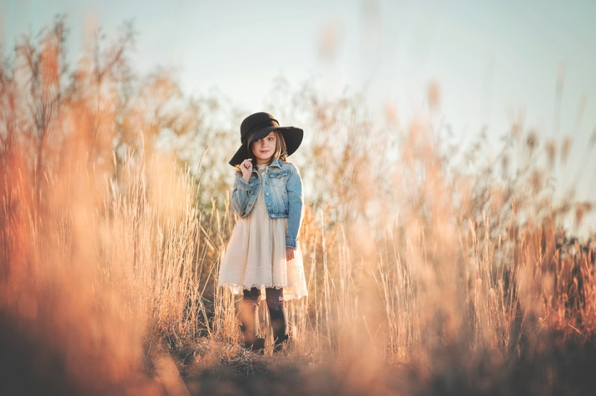 photo of girl in a hat standing in the grass by Becca Wohlwinder