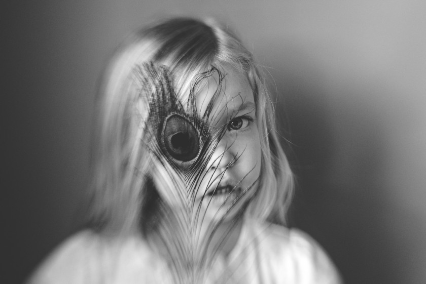 photo of girl with a feather in front of her face by Tiffany Kelly