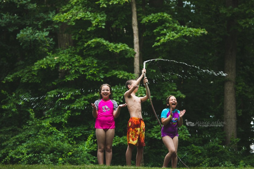 photo of kids playing in the water hose by Jessica Nelson