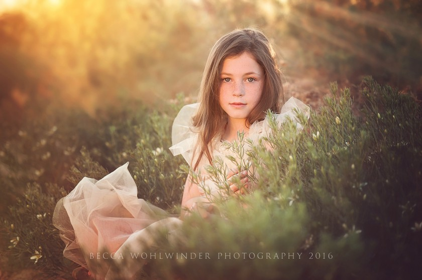 pic of girl sitting near a green bush by Becca Wohlwinder