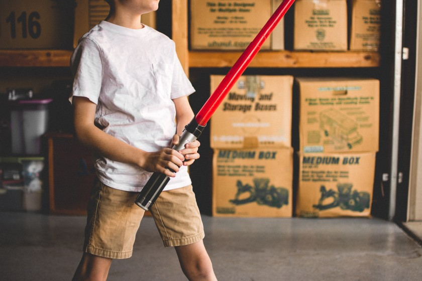 picture of boy holding a lightsaber in a garage by Kerry Lee