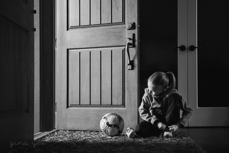 picture of girl putting on cleats next to a soccer ball by Gina Yeo