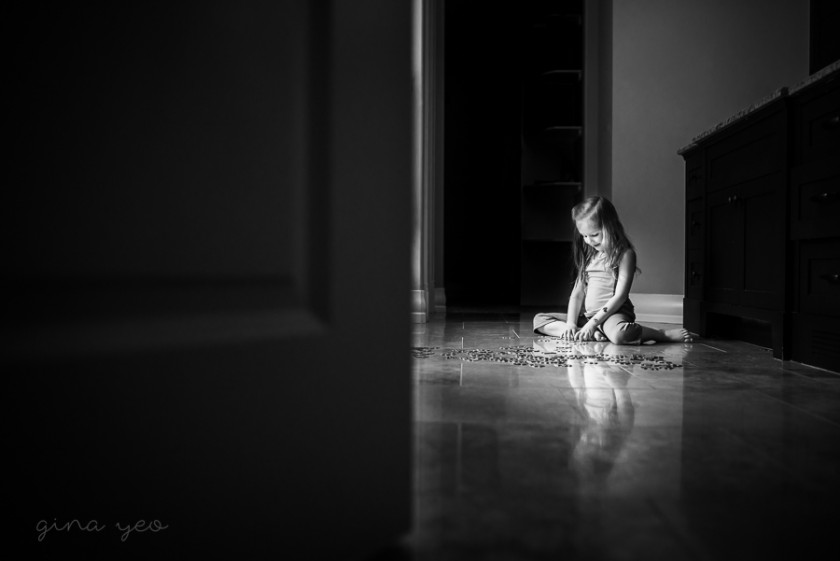picture of girl sitting on the floor doing a puzzle by Gina Yeo